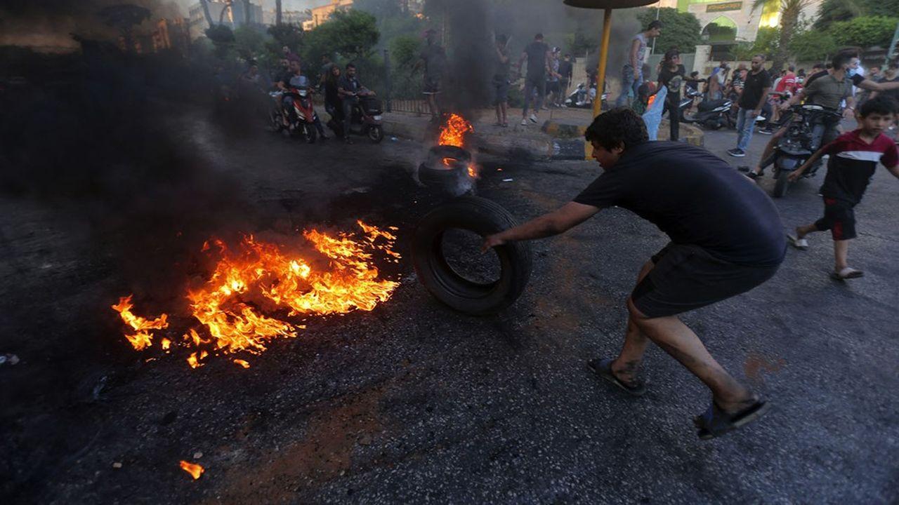 De jeunes Libanais brûlent des pneus pour bloquer une route, afin de protester contre les conditions de vie de plusen plusdifficiles.