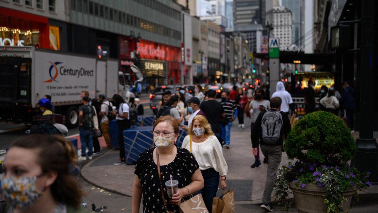 Des passants masqués à Manhattan, où les autorités entendent favoriser la vaccination.