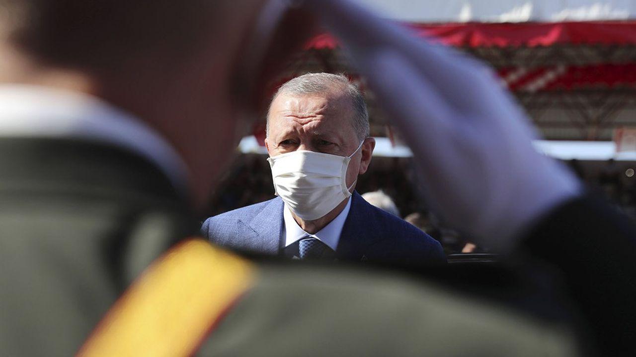 Le président turc, salué ici par une parade militaire, aimerait que le gouverneur de la banque centrale soit aussi au garde à vous pour accepter une baisse des taux d'intérêt turcs.