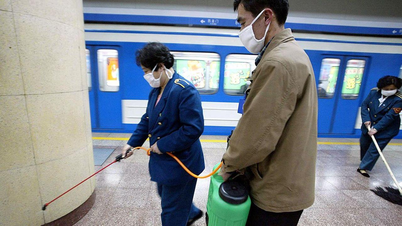Des employés désinfectent le métro de Pékin le 25avril 2003. Après des mois de déni, la Chine vient enfin de déclarer la guerre au Sras, un virus extrêmement virulent tuant une personne sur dix.