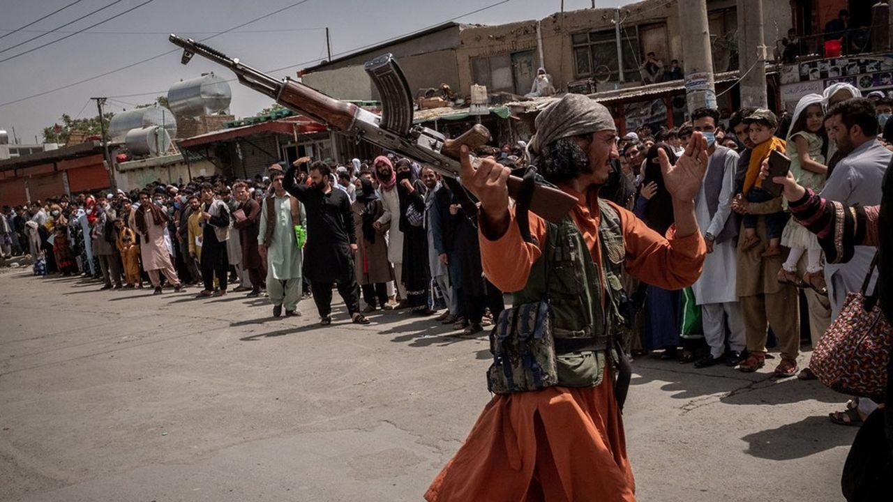 Un taliban menace de frapper une femme faisant la queue avec sa famille dans l'espoir d'accéder à l'aéroport de Kaboul contrôlé par les Américains.