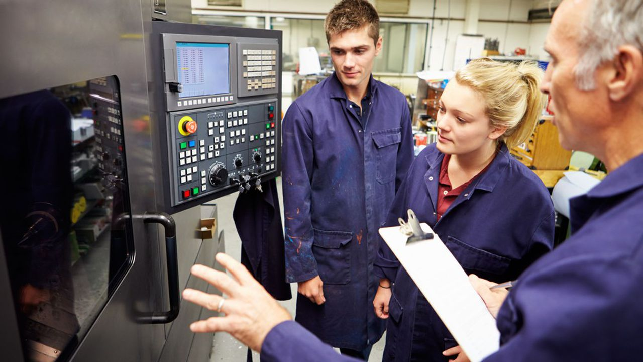 Un salarié explique le fonctionnement d'une machine à deux apprentis.