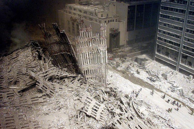 11 septembre 2001 : un groupe de pompiers s'avance dans les décombres recouverts de cendres, près de la base de la tour Sud du World Trade Center.