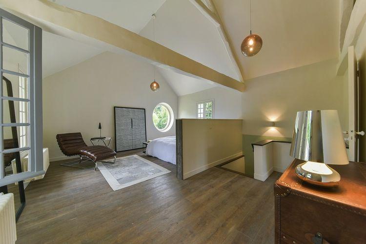 A l'étage, une chambre avec une belle hauteur sous plafond.