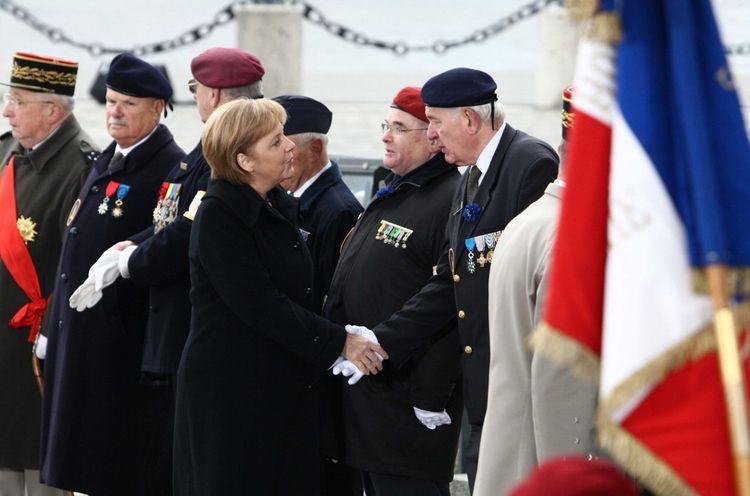 Angela Merkel et des vétérans de la Première Guerre mondiale devant la tombe du soldat inconnu sous l'Arc de triomphe.