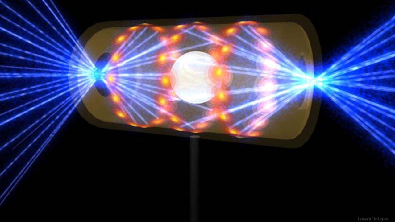 Vue d'artiste montrant la microbille de deutérium-tritium à l'intérieur de sa cavité en or. Les lasers entrant par les trous percés aux deux extrémités viennent frapper les parois internes. Le rayonnement ainsi produit fait imploser la microbille, déclenchant les réactions de fusion.