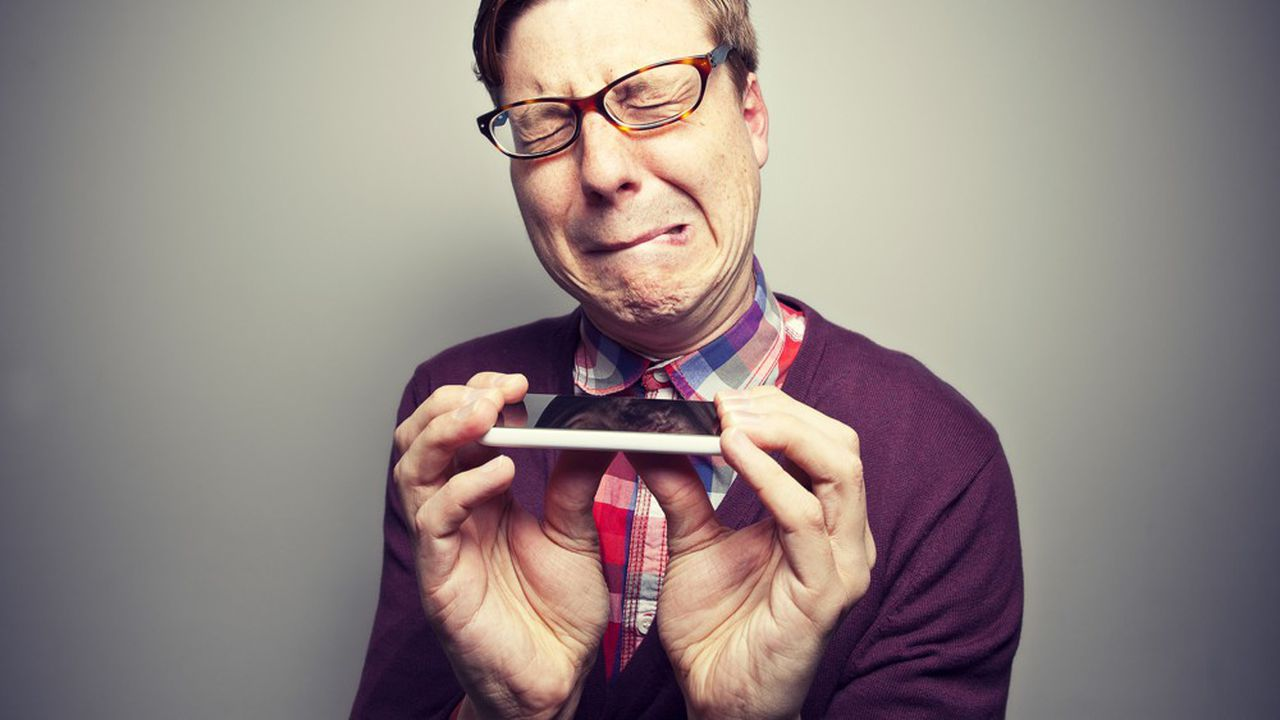 A nerdy geek tries to see if his smart phone will bend!