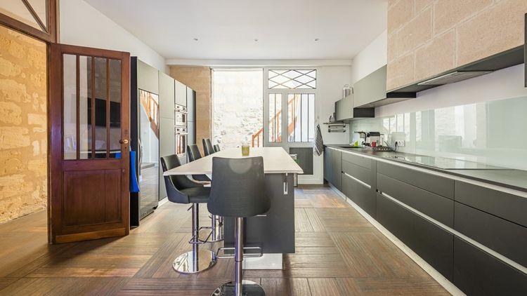 L'entrée donne sur un couloir qui dessert d'un côté, un grand salon et de l'autre, une salle à manger et cuisine contemporaine en enfilade.