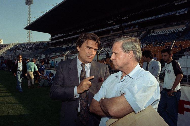 Le président du club de football de l'Olympique de Marseille, Bernard Tapie, s'entretient avec le manager de l'équipe, Michel Hidalgo, avant le match de football français de L1 entre le Paris Saint-Germain et l'OM au stade Vélodrome de Marseille en 1989.