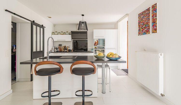 Dans le prolongement de l'entrée, on trouve une pièce de vie avec une cuisine ouverte, aménagée et équipée.